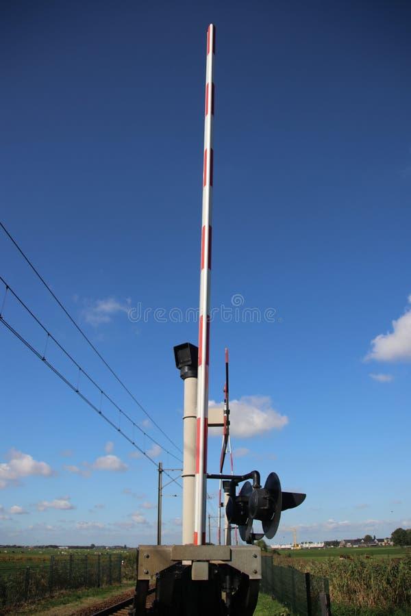 Cruzamento de estrada de ferro com barreiras, luzes vermelhas e sinos na única trilha em Nieuwerbrug nos Países Baixos fotografia de stock