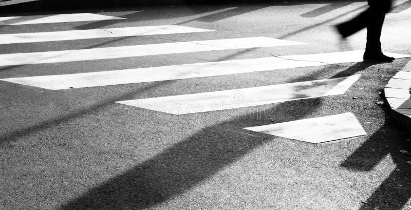 Cruzamento de zebra obscuro com silhueta e sombra da pessoa fotografia de stock royalty free