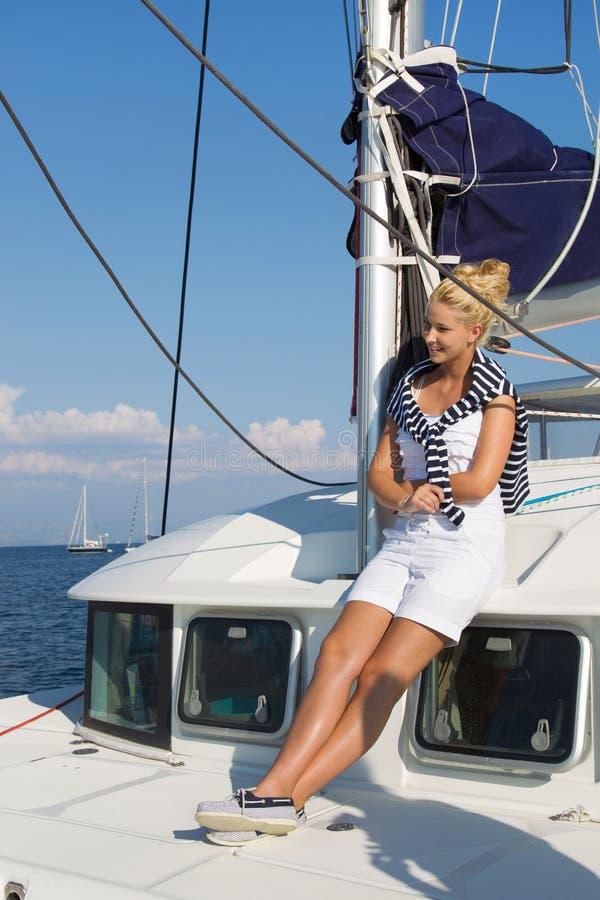 Cruzamento: Mulher da navigação em um barco de vela luxuoso no verão. imagem de stock