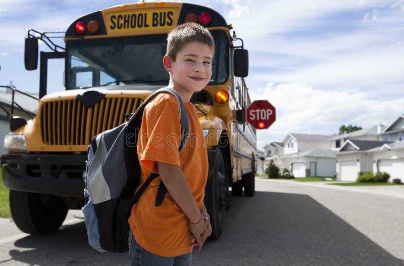 Cruzamento novo do menino na frente do auto escolar amarelo foto de stock