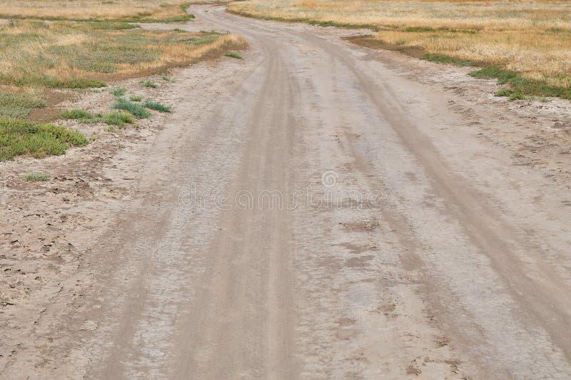 Cruzamento sujo rural empoeirada e de enrolamento de estrada o estepe com grama de secagem foto de stock