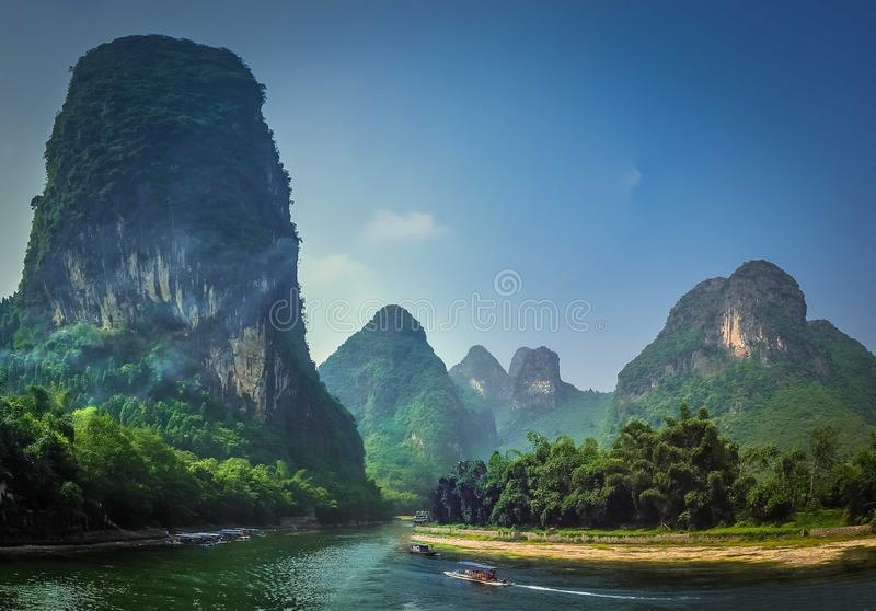 Cruzando o rio em um fundo de árvores densas verdes e de rochas altas fotos de stock