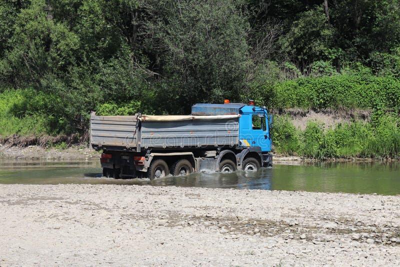 Cruzando um caminhão através de um rio raso da montanha Transporte dos bens em lugares difíciis de alcançar e em circunstâncias p imagem de stock