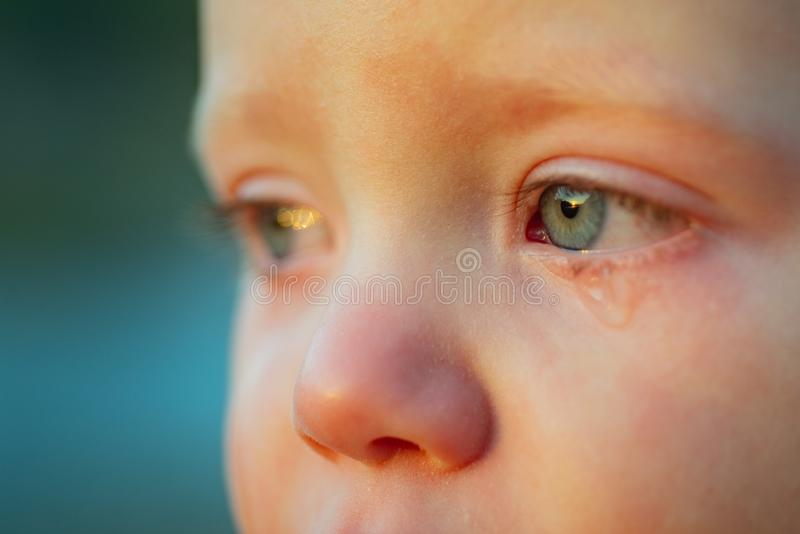 Cry baby with sky blue eyes. Little tender baby boy crying. Eye drop, tear drop of little sweetheart kid. Emotional baby stock images