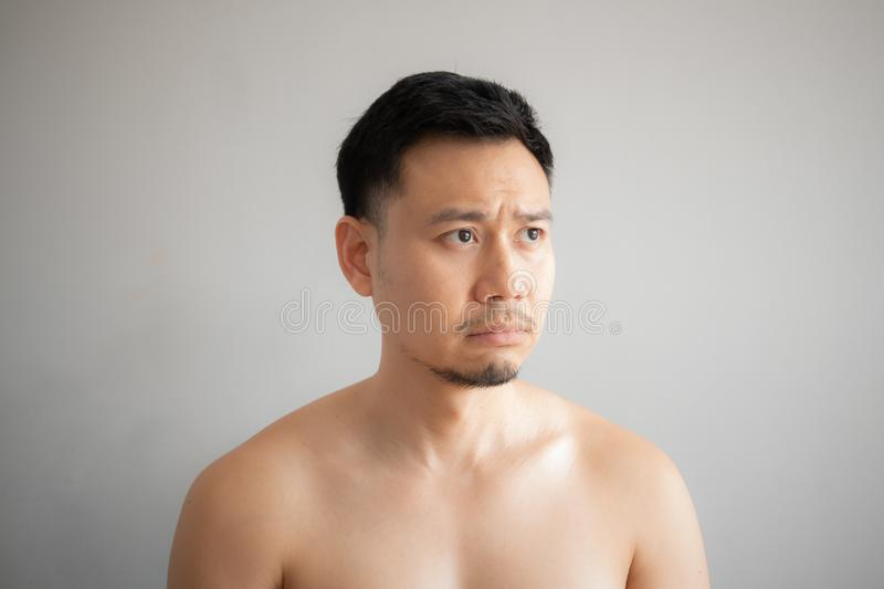 Cry and sad face of Asian man in topless portrait isolated on gray background royalty free stock photos