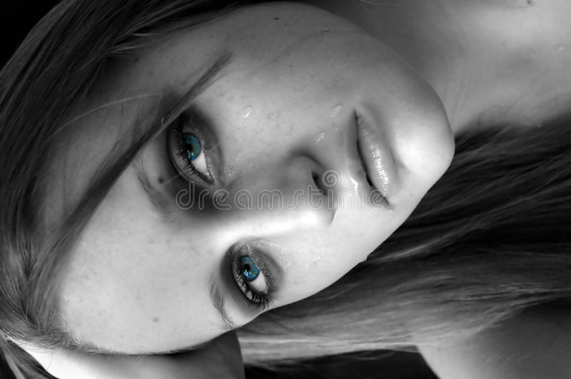 Crying aqua eyes. Girl crying with aqua blue eyes, the rest in black and white stock photography