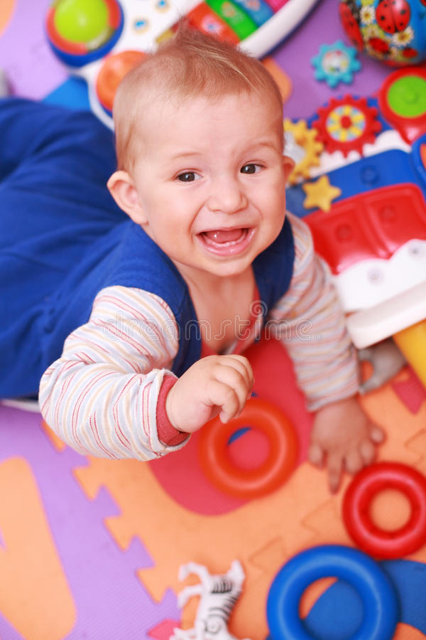 Crying baby. With lot of toys stock photography