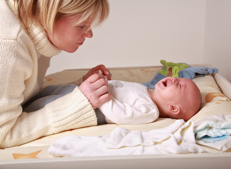 Crying baby. Mother trying to rest her baby royalty free stock photos