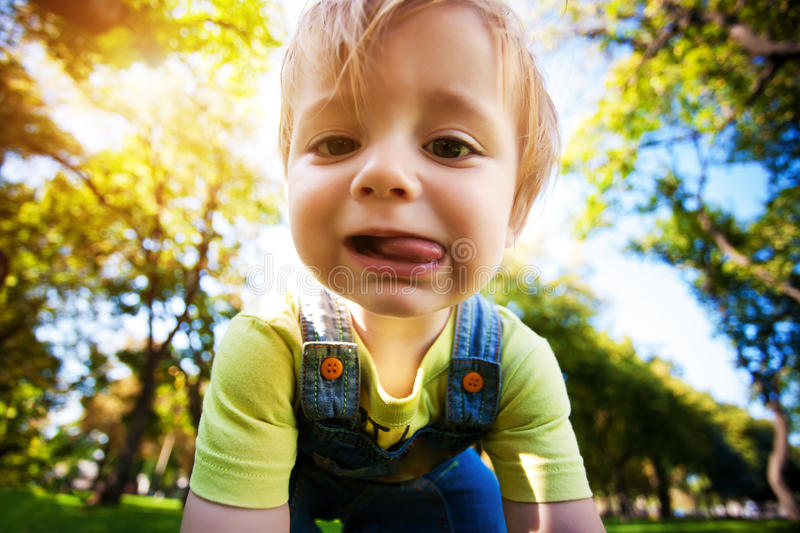 Download Crying Baby In A Beautiful Summer Park Stock Photo - Image of tongue, nature: 26654758