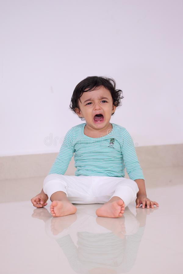 Crying baby boy sitting on floor. In living room ,close up royalty free stock images