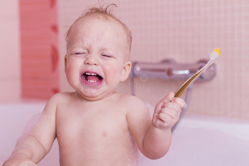 Crying baby boy with a toothbrush in a bathtub. Dissatisfied infant kid staying in a bath. royalty free stock photos