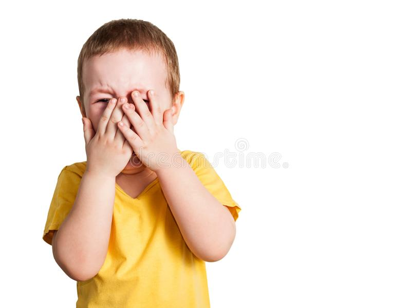 Crying baby boy in a yellow T shirt covers his face with hands and shouts, studio isolated on white background. Crying baby boy in a yellow T shirt covers face stock photos