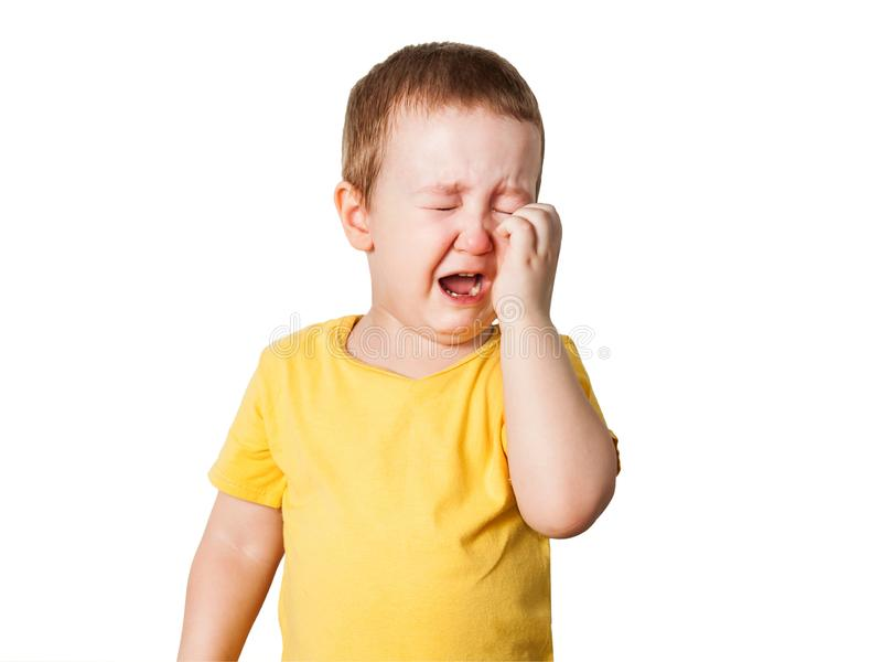 Crying baby boy in a yellow T shirt covers his face with hands and shouts, studio isolated on white background. Crying baby boy in a yellow T shirt covers face stock photo