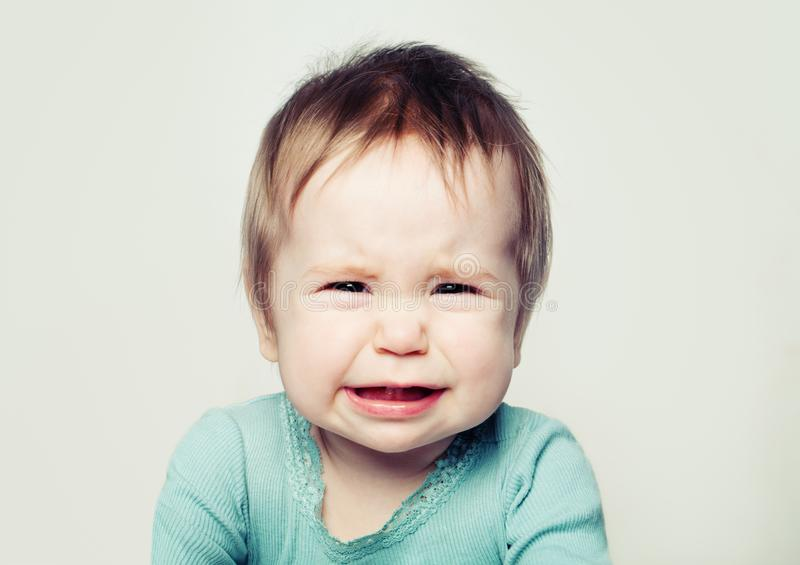 Crying baby face 6 months old on gray royalty free stock photo