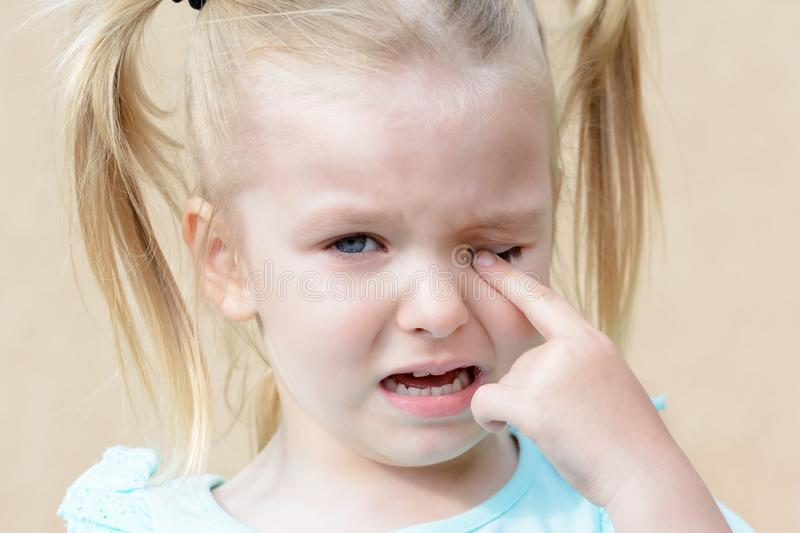 Crying baby. Hysterical girl with blond hair. stock image