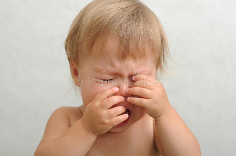 Crying baby rubbing her eyes. Screaming crying caucasian baby rubbing her eyes royalty free stock image