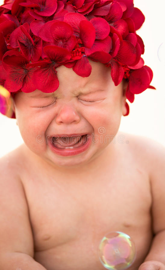 Crying Baby. Wearing a red flower hat royalty free stock image