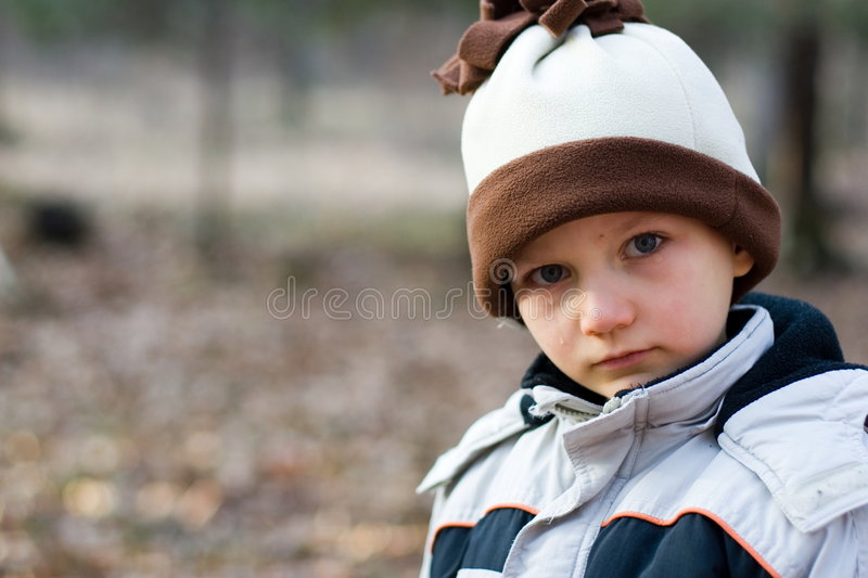 Crying Boy. Serious crying young boy, standing outside with a winter coat and hat on. Tear is on his right cheek stock images