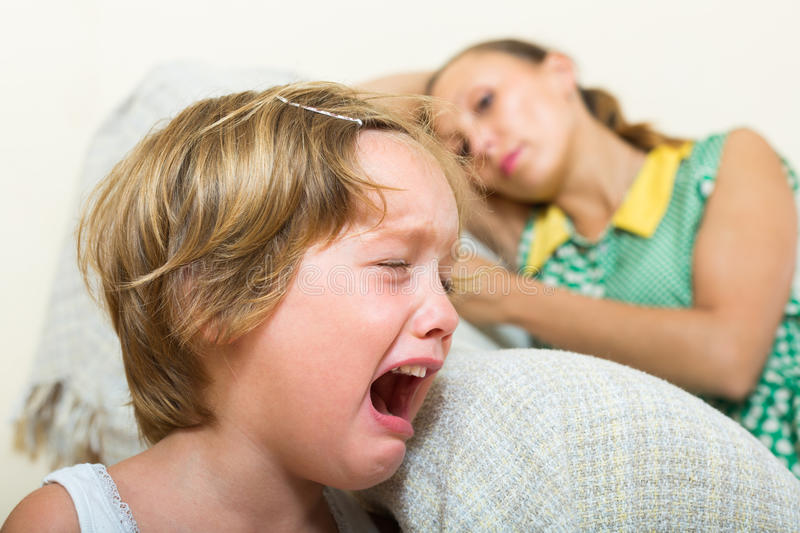 Crying child and mother at home royalty free stock photography