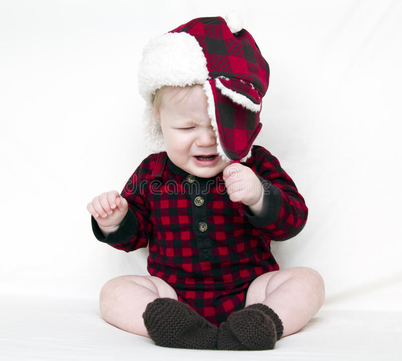 Crying Christmas baby trying to pull off hat royalty free stock photos
