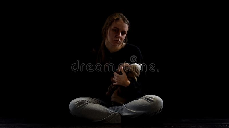 Crying depressed lady hugging teddy bear in darkness, obstetric violence victim. Stock photo royalty free stock photography