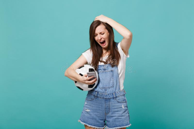 Crying displeased woman football fan with soccer ball using mobile phone, typing sms message, putting hand on head stock photography