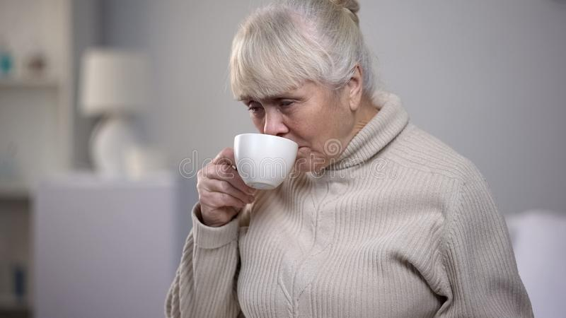Crying elderly woman drinking tea at nursing house, loneliness in old age. Stock photo royalty free stock images