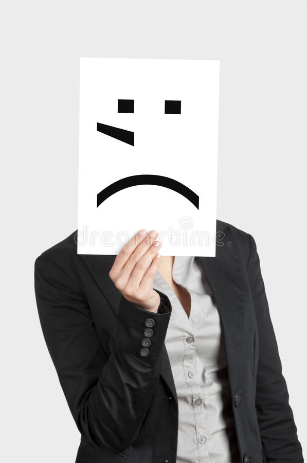 Crying emoticon. Woman showing a blank paper with a crying emoticon in front of her face royalty free stock images
