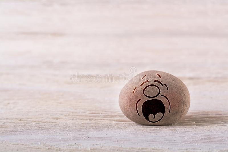 Crying emoticon. Stone face on white wood background with free space for your text royalty free stock photo