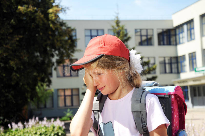 Crying girl. In front of the school stock photos