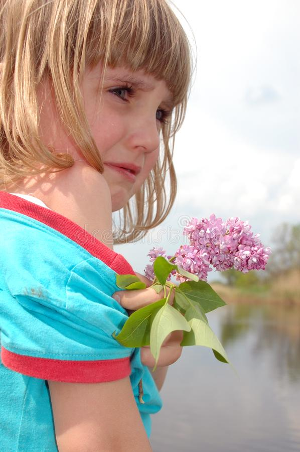 Crying girl with lilac royalty free stock image