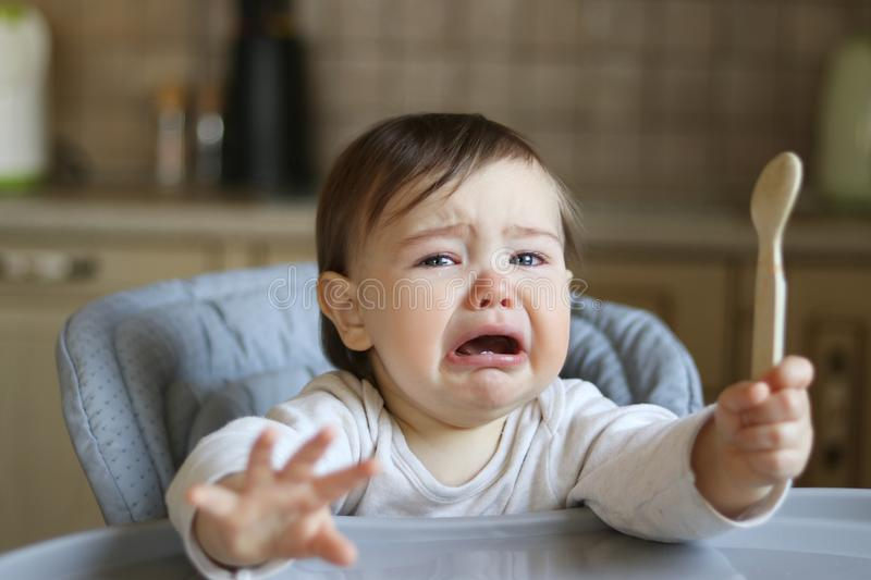 Crying hungry little baby with tears in eyes sitting in the high feeding chair with spoon royalty free stock photography