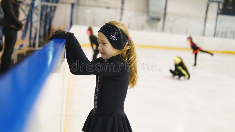 Crying little girl in figure skating training at indoor rink. Crying little girl in black headband in figure skating training at indoor rink stock photo