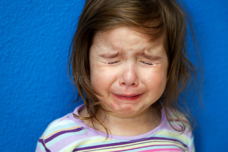 Crying Little Girl With Chicken Pox. A little girl whose Chicken Pox are just starting to show stands crying her eyes out. She looks so sad with tight clenched royalty free stock photos
