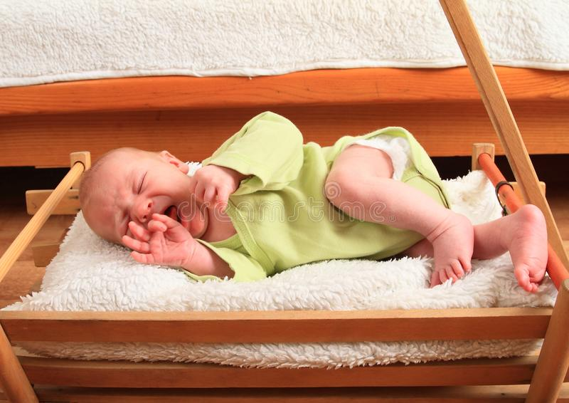 Crying newborn baby boy lying in carriage stock photo