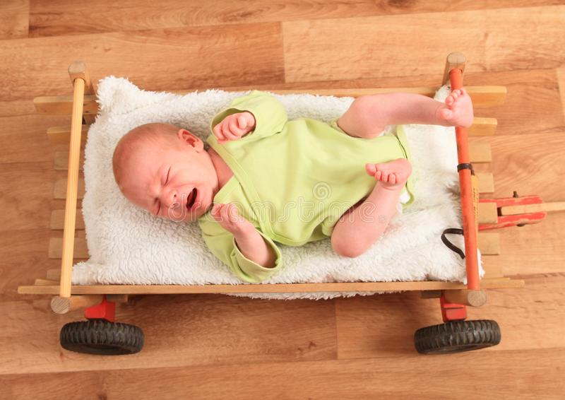 Crying newborn baby boy lying in carriage royalty free stock images