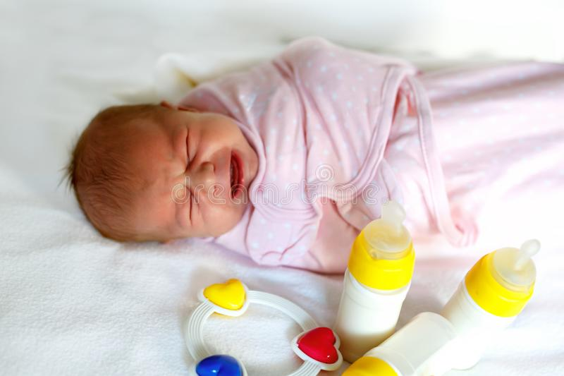 Crying newborn baby girl with nursing bottles. Formula drink for babies. royalty free stock images