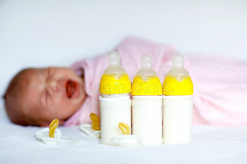 Crying newborn baby girl with nursing bottles. Formula drink for babies. stock photo