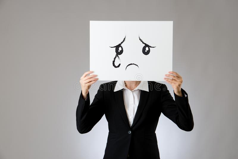 Crying and sadness face expression drawing. One blank white poster holding by a businesswoman. isolated on gray background. business office company concept royalty free stock images