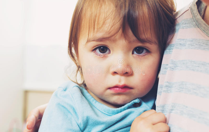 Crying toddler girl. Being consoled by her mother stock photo
