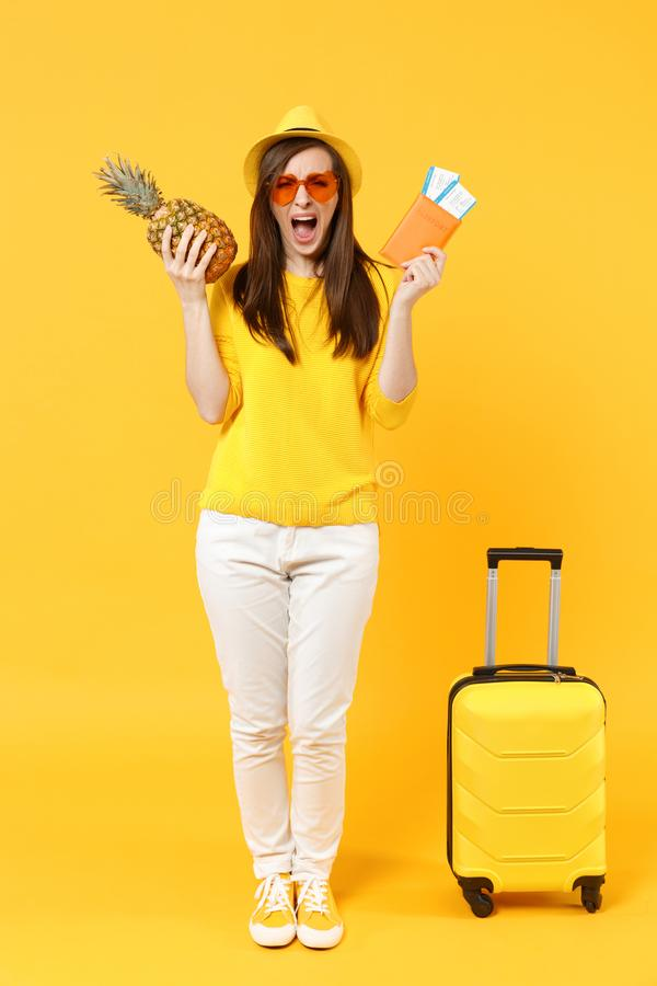 Crying traveler tourist woman in hat holding passport tickets, fresh pineapple fruit isolated on yellow orange. Background. Passenger traveling abroad on stock photo