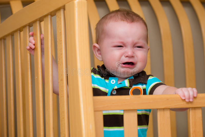 Crying unhappy baby standing in crib royalty free stock image