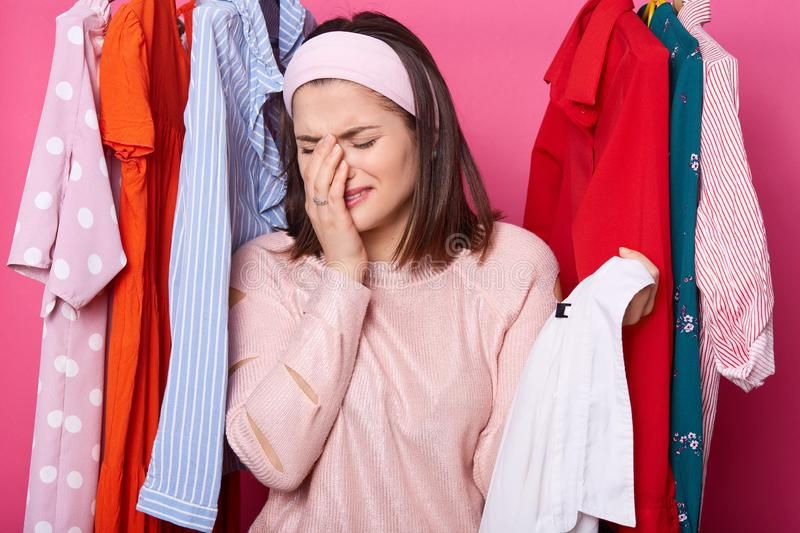 Crying woman keeps right hand near her face, holds hanger with white shirt while standing at her wardrobe. Dark haired woman has stock photo