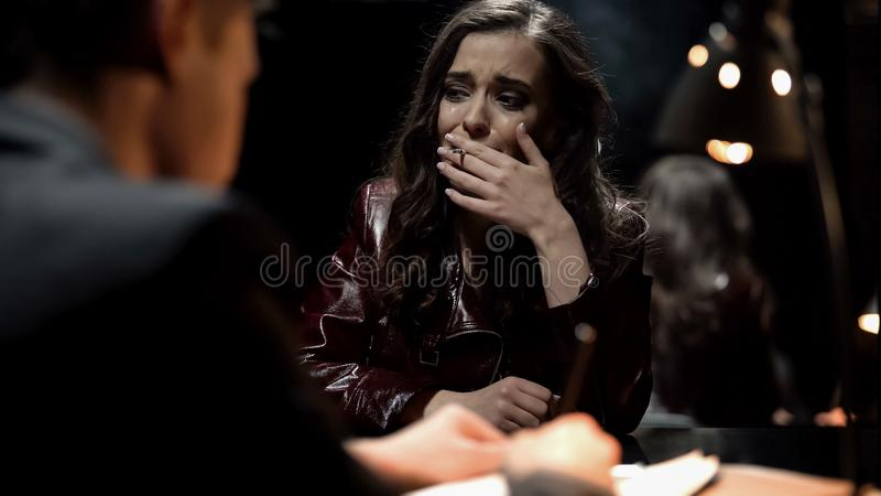 Crying woman smoking cigarette in interrogation room, giving evidence to cop. Crying women smoking cigarette in interrogation room, giving evidence to cop, stock stock image