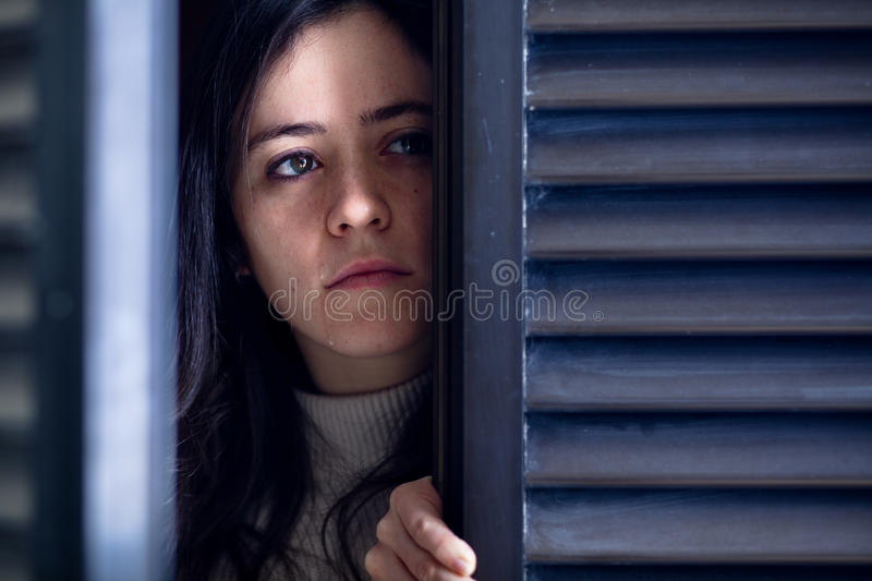 Crying Woman Watching through a Window royalty free stock photography