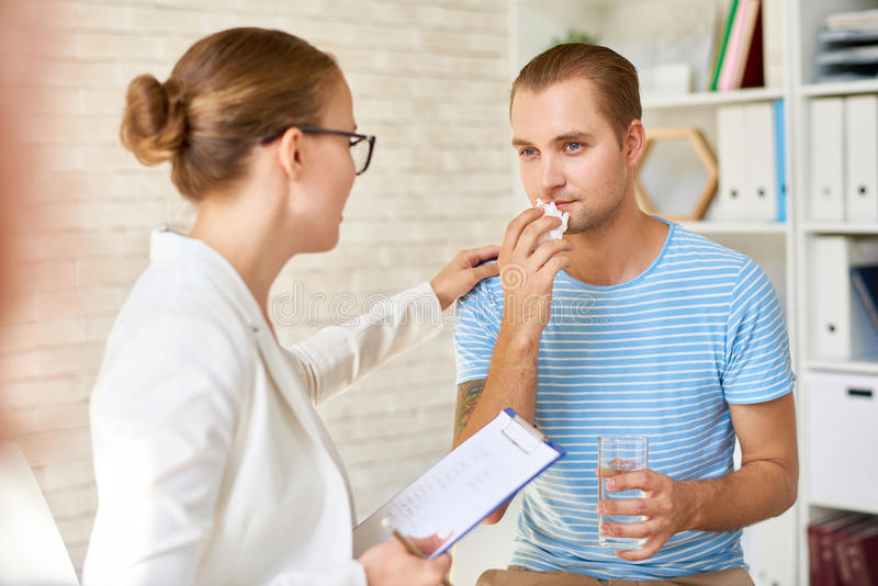 Crying Young Man in Support Group. Portrait of female psychiatrist comforting crying young men suffering from despair during group therapy session, providing royalty free stock images