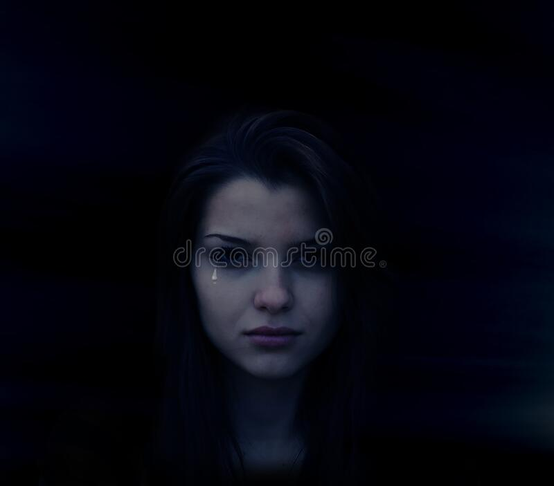 Crying young woman in shadows stock images