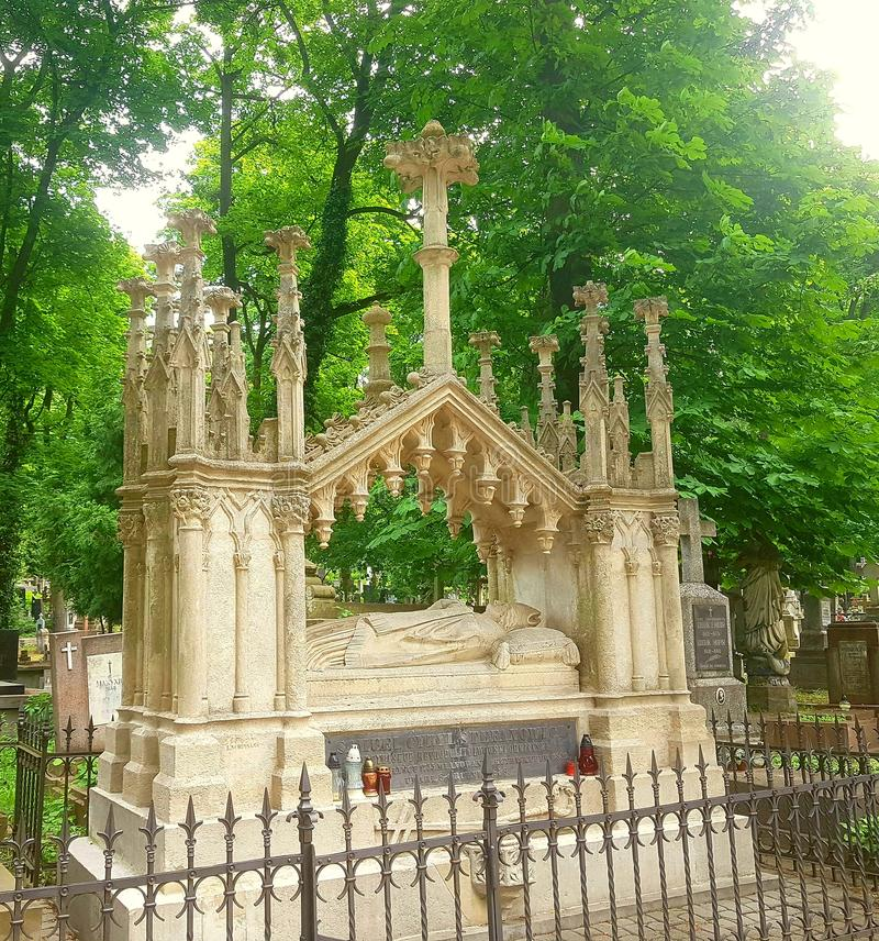The crypt in which lies a man of high rank. Above it is a lot of columns. Around the green trees and grass. stock image