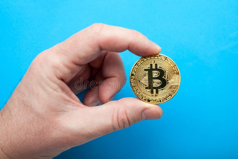 Crypto currency The bitcoin in hand on a blue background stock photo