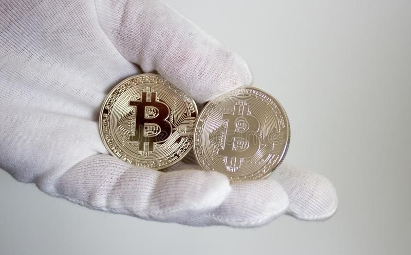 Crypto currency bitcoin on hand in white glove 2. On hand in white glove are silver coins of a digital crypto currency - Bitcoin royalty free stock photos